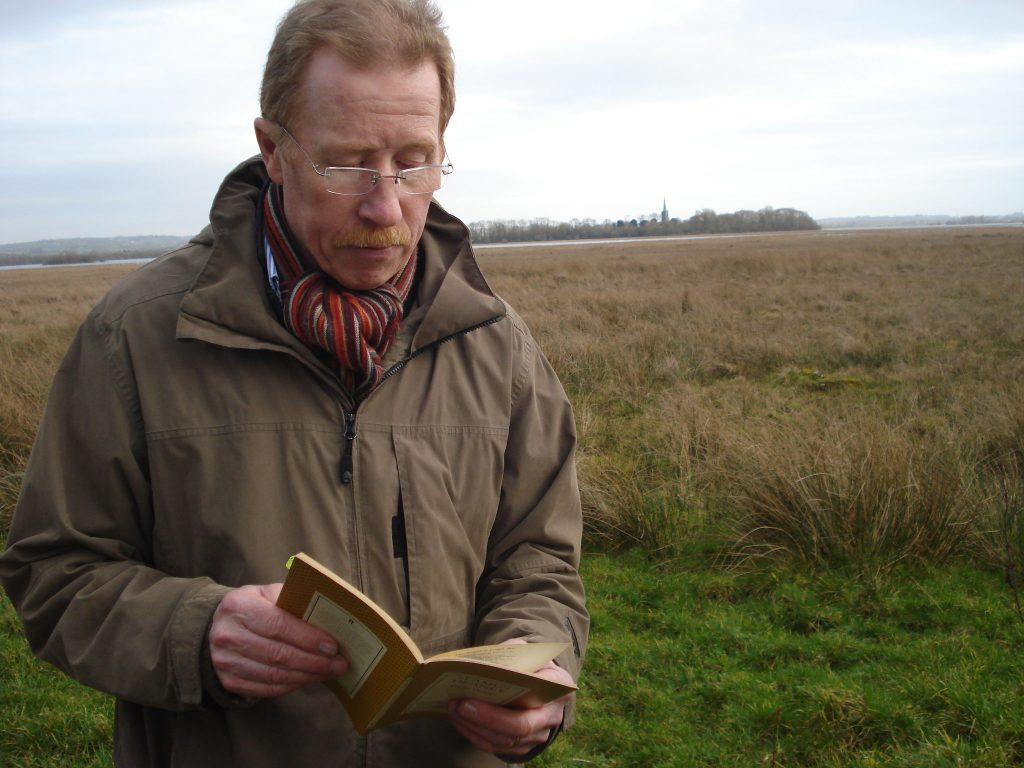 Eugene Kielt of Laurel Villa Guest House reading on The Strand at Lough Beg - Eugene is a Blue Badge guide and expert in Seamus Heaney's poetry.